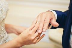 Jeune mariée plaçant une bague de fiançailles Photographie stock libre de droits