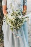 Jeune mariée portant le bouquet bleu-clair de participation de robe l'épousant photo stock