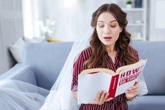 Jeune mariée portant le livre de lecture argenté gentil de boucles d'oreille Image stock