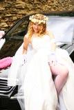 Jeune mariée posant près d'une voiture Photo stock