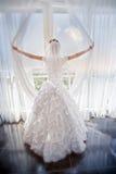 Jeune mariée près de fenêtre Image stock