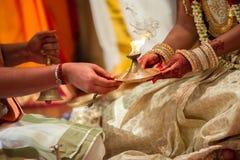 Jeune mariée recevant la lampe du prêtre à un mariage indou tamoul Photos libres de droits