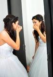 Jeune mariée regardant dans le miroir photographie stock