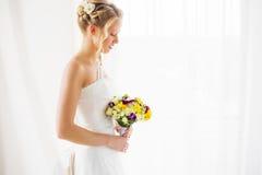 Jeune mariée regardant vers le bas ses fleurs de mariage Photographie stock libre de droits