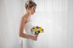 Jeune mariée regardant vers le bas son bouquet de mariage Photographie stock libre de droits