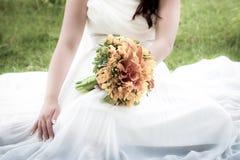 Jeune mariée retenant un bouquet Photographie stock libre de droits