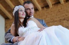 Jeune mariée s'appuyant sur le marié dans un entrepôt dans les ruines Image libre de droits