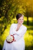 Jeune mariée s'asseyant avec des fleurs sur l'herbe en parc photographie stock libre de droits