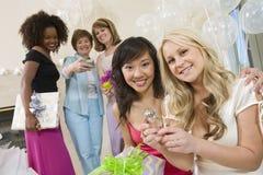 Jeune mariée s'asseyant avec son ami montrant la grande bague de fiançailles Photographie stock
