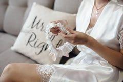Jeune mariée s'asseyant dans le peignoir Photographie stock libre de droits
