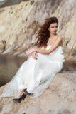Jeune mariée s'asseyant dans une terre stérile Image libre de droits