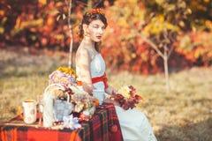 Jeune mariée s'asseyant en parc Photographie stock