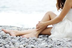 Jeune mariée s'asseyant par la mer Image libre de droits