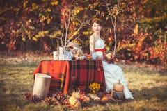 Jeune mariée s'asseyant près de la table dans la forêt d'automne Image stock