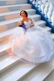 Jeune mariée s'asseyant sur les escaliers Photos stock