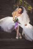 Jeune mariée s'asseyant sur les escaliers Photographie stock