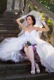 Jeune mariée s'asseyant sur les escaliers Images stock