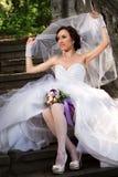 Jeune mariée s'asseyant sur les escaliers Photographie stock libre de droits