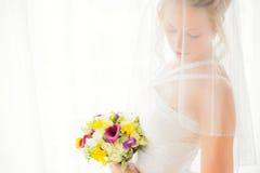 Jeune mariée se cachant derrière le voile avec des fleurs dans des ses mains Photographie stock