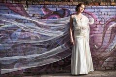 Jeune mariée se tenant près du mur coloré avec le voile de vol Photo stock