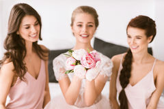 Jeune mariée sortie s'asseyant dans la chambre à coucher avec ses demoiselles d'honneur Image stock