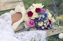 Jeune mariée sur l'oscillation avec les chaussures et le bouquet Photo libre de droits