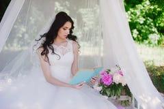 Jeune mariée sur la nature de lire un livre, décor, pivoines, fleurs, mode de vie, mariage, famille, amour Photographie stock
