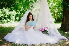 Jeune mariée sur la nature de lire un livre, décor, pivoines, fleurs, mode de vie, mariage, famille, amour Photos libres de droits