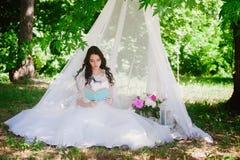Jeune mariée sur la nature de lire un livre, décor, pivoines, fleurs, mode de vie, mariage, famille, amour Photographie stock libre de droits
