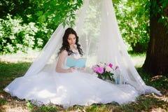 Jeune mariée sur la nature de lire un livre, décor, pivoines, fleurs, mode de vie, mariage, famille, amour Images libres de droits