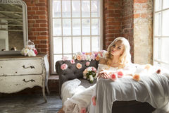 Jeune mariée sur le sofa de vintage avec des fleurs Photographie stock libre de droits