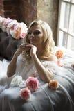Jeune mariée sur le sofa de vintage avec des fleurs Image libre de droits