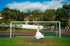 Jeune mariée sur le terrain de football Photographie stock libre de droits