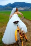Jeune mariée sur le vélo orange dans la belle robe de mariage avec la dentelle dans le paysage Proue d'étoile bleue avec la bande Photo stock