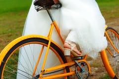 Jeune mariée sur le vélo orange dans la belle robe de mariage avec la dentelle dans le paysage Proue d'étoile bleue avec la bande Images libres de droits