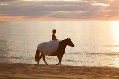 Jeune mariée sur un cheval au coucher du soleil par la mer Photographie stock