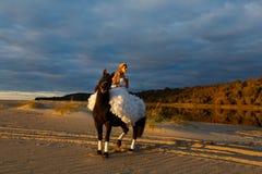 Jeune mariée sur un cheval au coucher du soleil par la mer Photos stock
