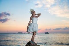 Jeune mariée sur une plage tropicale avec le coucher du soleil à l'arrière-plan Image libre de droits