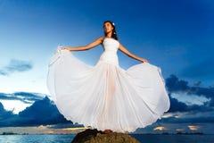 Jeune mariée sur une plage tropicale avec le coucher du soleil à l'arrière-plan Photographie stock libre de droits
