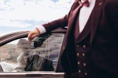 Jeune mariée sur une séance photos l'épousant dans la voiture photo libre de droits