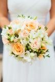 Jeune mariée tenant la pêche Coral Rose Bouquet Image stock