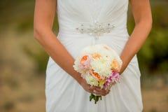 Jeune mariée tenant le bouquet blanc des fleurs Images stock