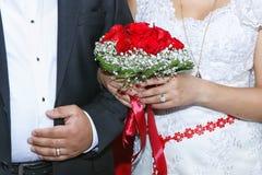 Jeune mariée tenant le bouquet coloré de fleurs avec ses mains le jour du mariage Photos stock