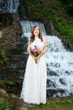 Jeune mariée tenant le bouquet coloré devant une cascade Images libres de droits