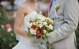 Jeune mariée tenant le bouquet de fleur de mariage des roses blanches image stock