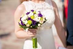 Jeune mariée tenant le bouquet de mariage Photographie stock libre de droits