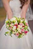 Jeune mariée tenant le bouquet de mariage Photos stock