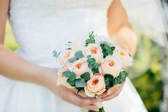 Jeune mariée tenant le bouquet de mariage avec les roses rouges Image libre de droits