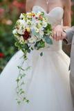 Jeune mariée tenant le bouquet de mariage des fleurs et des roses colorées Image stock