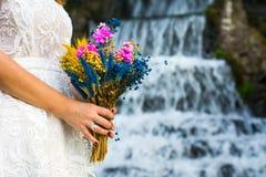 Jeune mariée tenant le bouquet de mariage devant une cascade Image libre de droits